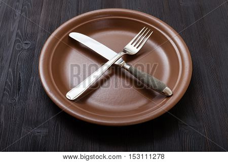 Brown Plate With Crossing Knife, Spoon On Dark