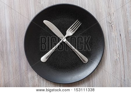 Top View Of Black Plate With Flatware On Gray