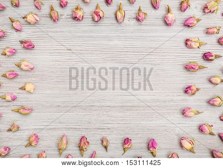 Frame From Rose Flower Buds On Wooden Table