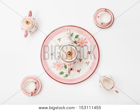 Above View Of Pink Porcelain Tea Set On White