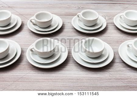 Several White Cups And Saucers On Gray Brown Table