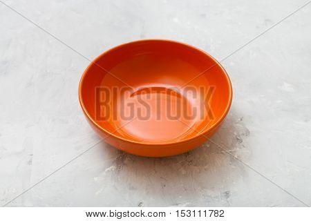 Orange Bowl On Gray Concrete Plate