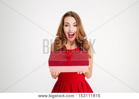 Cheerful attractive blonde woman in red dress holding present isolated over white background