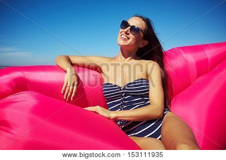 A lady wearing sunglasses and letting her hair down and having a great time on this shiny day