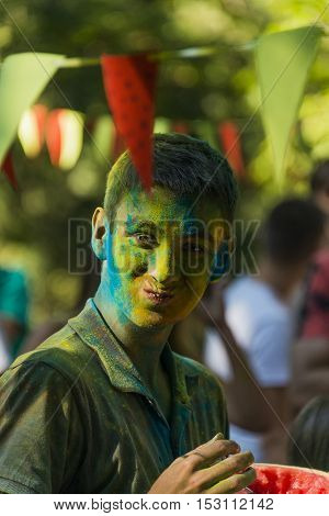 Lviv Ukraine - August 28 2016: Funny young man with a painted face eating watermelon during the festival of color in a city park in Lviv.