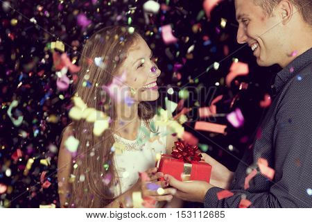 Beautiful young couple in love having fun at New Year's Eve Party guy giving a present to his girlfriend at midnight