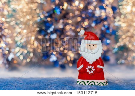 Close-up Figurine toy Santa Claus on colorful golden and blue bokeh background. New Year or Christmas picture.