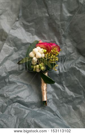 Boutonniere on a gray crumpled sheet of paper. Stylish Decorating for masculine image.
