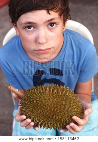preteen handsome boy with durian fruit with bad smell close up photo