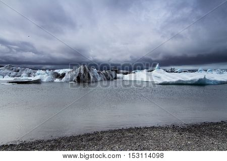 Glacier in lagoon with storm clouds above in Iceland