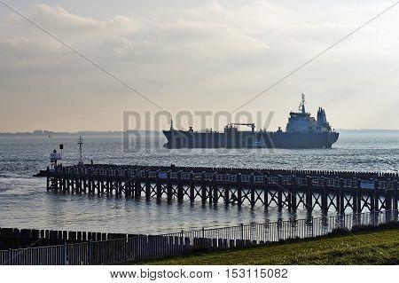 Freight Ship Entering Port Of Vlissingem Against Backlight