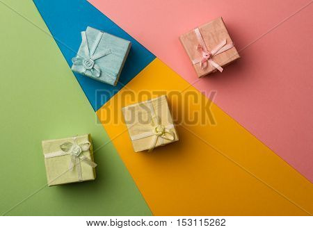top view of colored gift boxes on minimal background of different kinds of paper textures