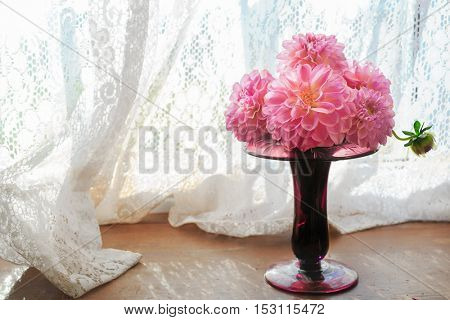 Pink dahlias in an antique glass vase.
