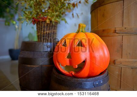 Halloween pumpkin head jack lantern on wooden barrel