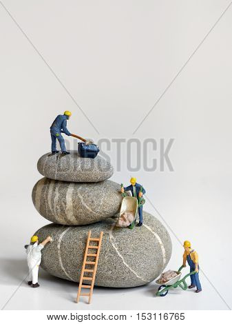 Pebbles stack and figurines of construction workers