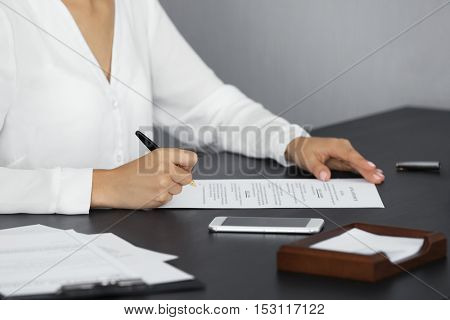 Woman signing important document in modern office