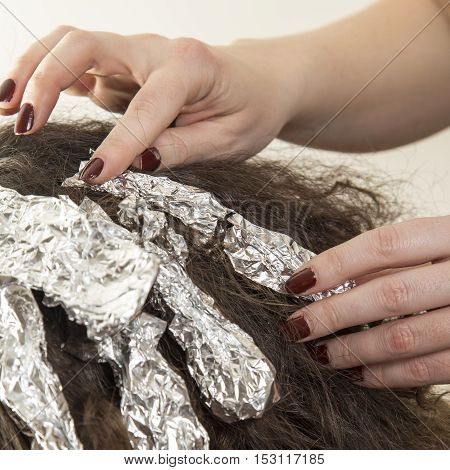 Highlighting woman client's hair in beauty parlor hairdressing salon