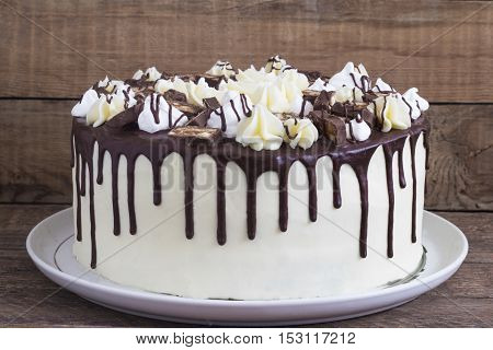 Round homemade cake with a meringue and chocolate on a wooden background