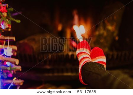 Woman feet in wool socks warming by fireplace, winter holidays concept
