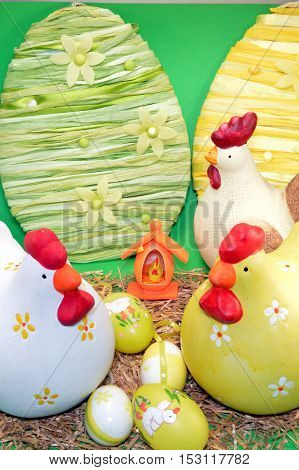 Three hens of Easter with eggs on the straw.