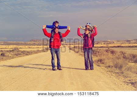 family with two kids walking on scenic road, tourism and travel