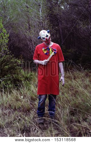 a scary evil clown, wearing a dirty costume, with a big knife in his hand, in the woods