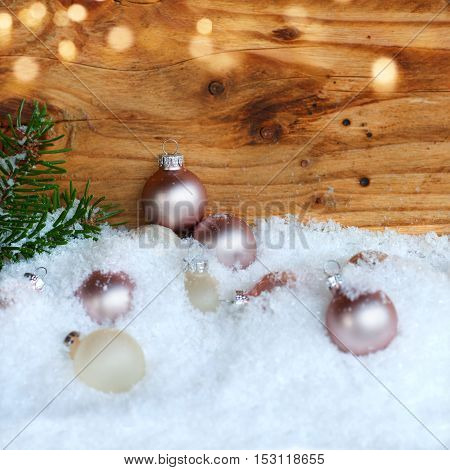 Christmas balls with pine branch In the snow in front of a wooden wall