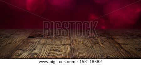 Abstract background in red with bokeh in front of a wooden table for Valentines day