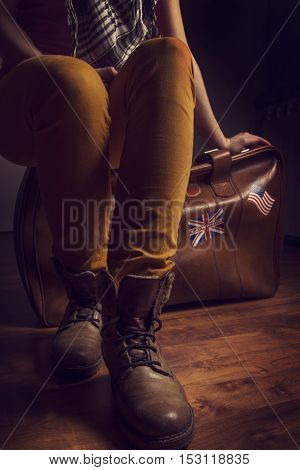 Retro woman in brown shoes sitting on a vintage leather suitcase