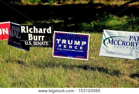 Pittsboro NC - October 23 2016: Political advertising campaign signs for both local and national candidates at the intersection of two rural roads