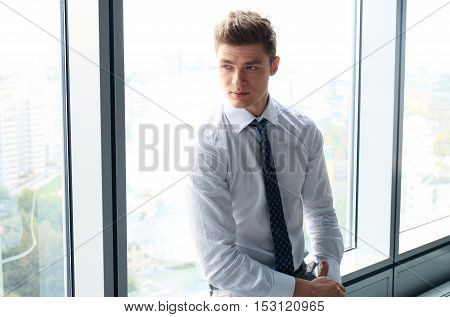 Handsome businessman looking through window in office