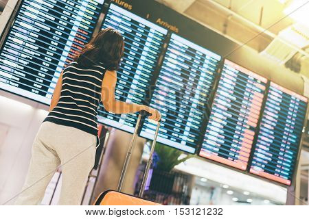 Asian woman traveler looking at flight information screen in an airport holding suitcase travel or time concept warm light effect