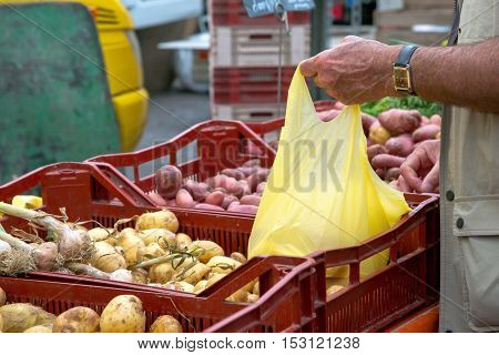 mature man buying new potatoes with plastic pocket from local market