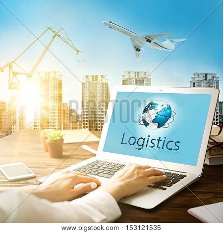 Female hands working with laptop, word LOGISTICS on screen. Cityscape background. Transport logistic concept.