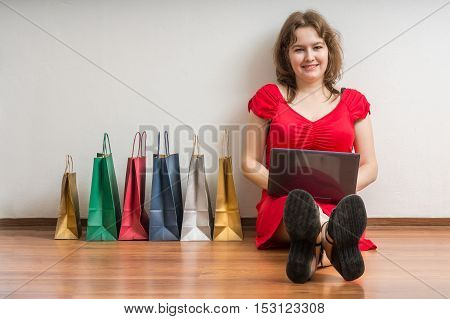 Young Woman Is Sitting On Floor With Laptop And Shopping Online