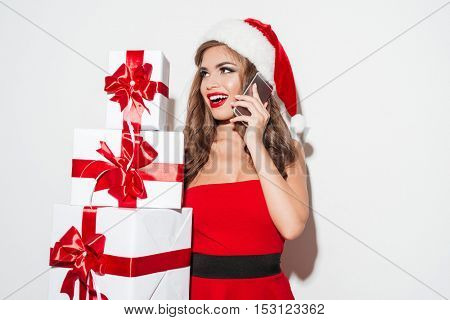 Portrait of a happy young woman in red santa claus dress and hat holding stack of presents and talking on mobile phone isolated on the white background