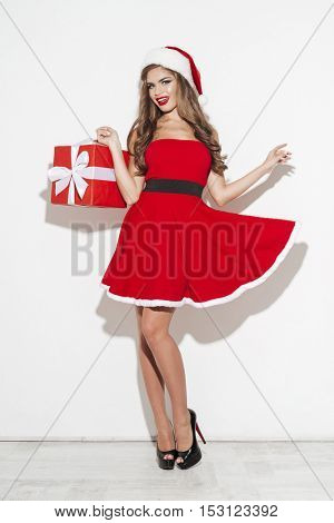 Full length portrait of smiling brunette woman in red santa claus dress holding xmas present isolated on the white background