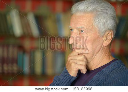 Portrait of thoughtful elderly  man near bookshelves background