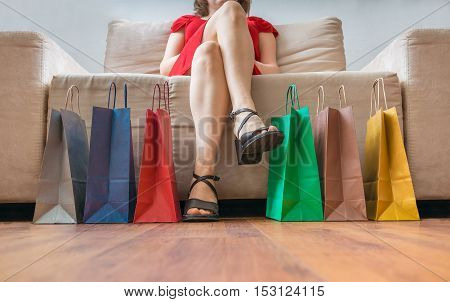 Shopping And Consumerism Concept. Legs Of Young Woman Sitting On