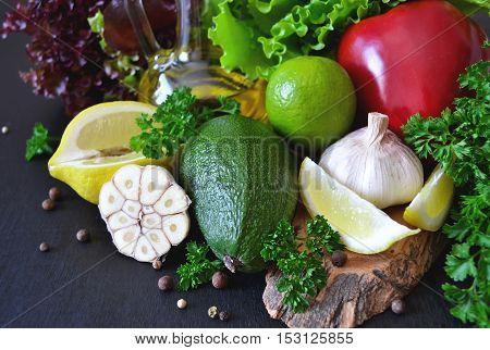 Fresh ripe vegetables olive oil lettuce on a black background