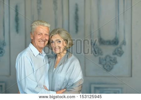 Happy smiling old couple near wall in room