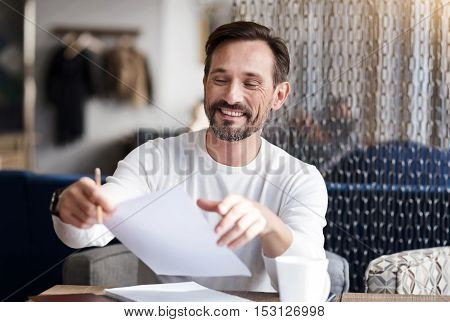 Sign here. Happy handsome bearded man holding pencil and taking paper while sitting in the modern office.