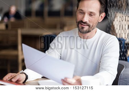 Attentively reading. Handsome bearded man sitting in office reading important document and happily smiling.