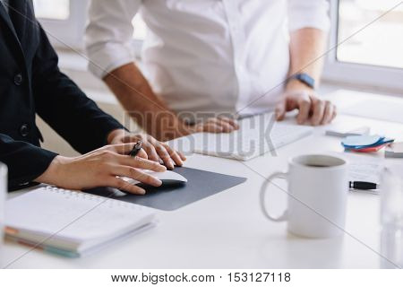 Close up shot of businesswoman using computer mouse with male colleague standing by work desk. Two business associates working together at office desk with focus on female hands.