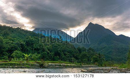 Clouds rolling between the Majesty of Mountain Kinabalu and Mountain Nungkok during sunset at Tambatuon village,Kota Belud,Sabah Land Below The Wind.