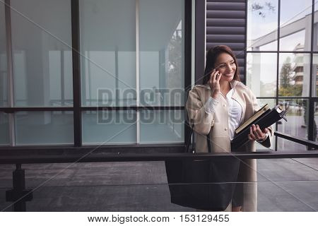 Company CEO busy talking on phone while holding folders