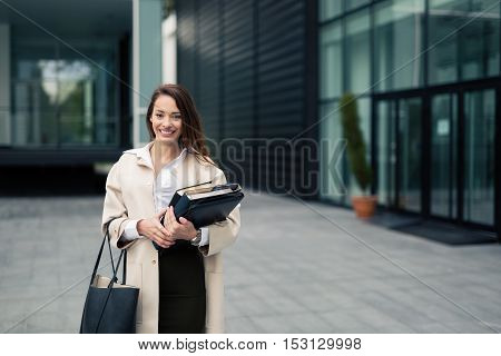 Successful young happy businesswoman outdoors holding files