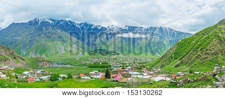 The mountain resort of Stepantsminda (former Kazbegi) located in the mountain valley and surrounded by the huge mountains of Higher Caucasus Range Georgia.