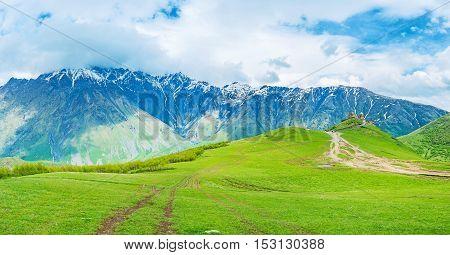 The long way through the green highland meadows to the medieval Gergeti Trinity Church at the foot of Kazbek Mount Kazbegi National Park Georgia.