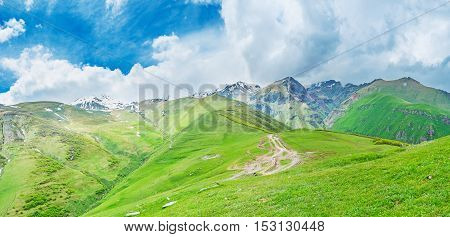The green hills and mountain slopes of Kazbegi National Park at the foot of Kazbek Mount covered with clouds Gergeti Georgia.